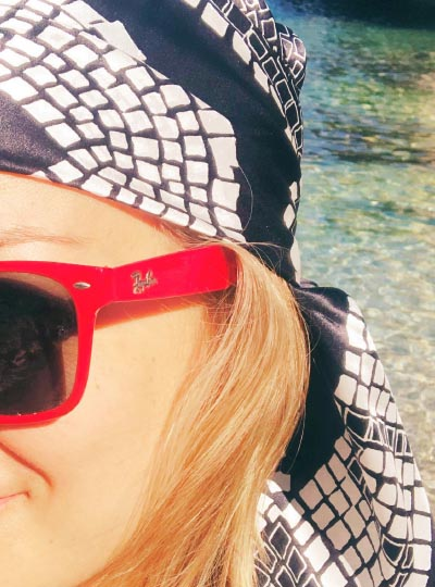 12 woman wearing a silk headscarf wrapped around her head at the beach with red sunglasses